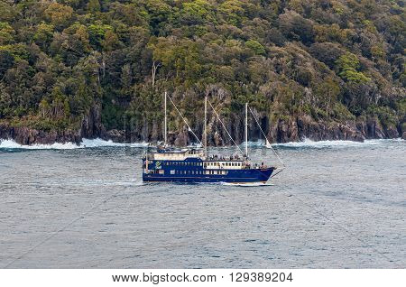 Milford Sound New Zealand - November 14 2014: The Milford Mariner Ship cruising in Milford Sound Fjord New Zealand. This fiord is considered as one of the most scenic places in the world.