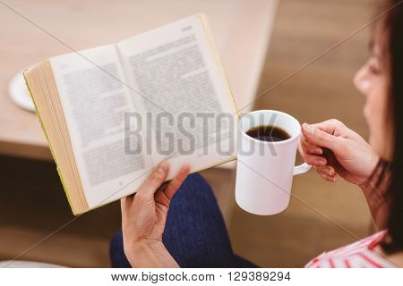 Cropped image of woman reading book while holding coffee cup at home