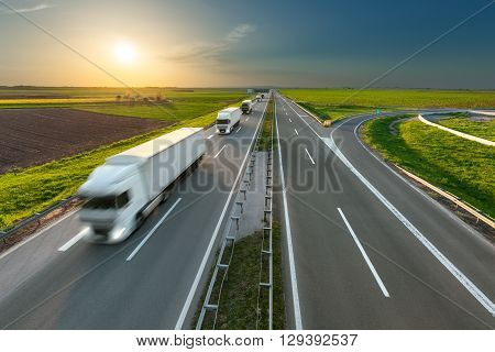 Many new modern trucks in a row driving towards the sun at idyllic sunny day. Fast blurred motion drive on the freeway. Freight scene on the motorway near Belgrade Serbia.