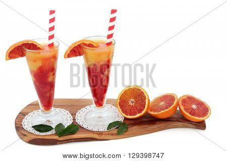 Blood orange fruit juice drink in glasses on doilies with striped straws on an olive wood board over white background. High in vitamins, anthocyanins and antioxidants.