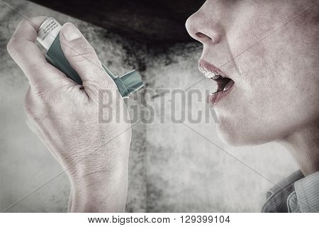 Close up of a woman using an asthma inhaler against image of room corner