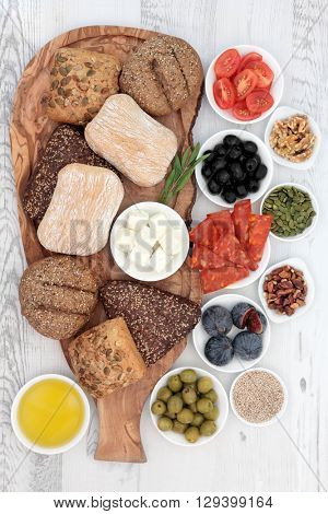 Italian food snacks with bread rolls on an olive wood board with salami, feta cheese, figs, nuts, seeds and oil over distressed wooden background.