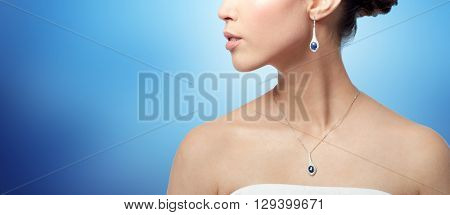 beauty, jewelry, wedding accessories, people and luxury concept - close up of beautiful asian woman or bride with earring and pendant over blue background