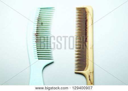 Old dirty and broken colorful combs on gray background.