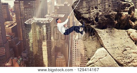 Businessman pulling rope while sitting on cube against image of a city landscape