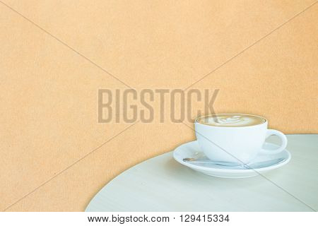 White cup of coffee latte on brown paper backgound stock photo