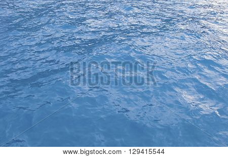 Ripples on a blue surface of the sea close up.