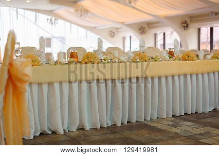 Wedding table in a celebratory bright hall. Floral decoration on the table. Arrangement of yellow roses and pearl beads on a wedding table.