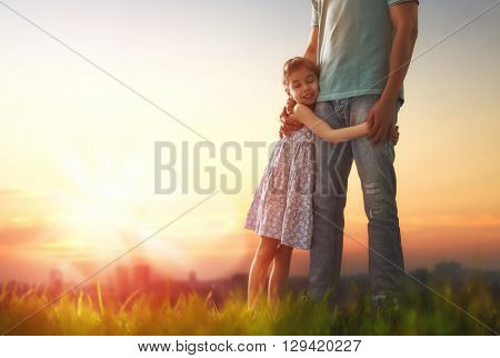 Happy loving family. Father and his daughter child girl playing and hugging outdoors. Cute little girl hugs daddy. Concept of Father's day.