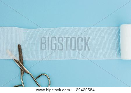 Medical scissors with unrolled gauze, on light blue background.