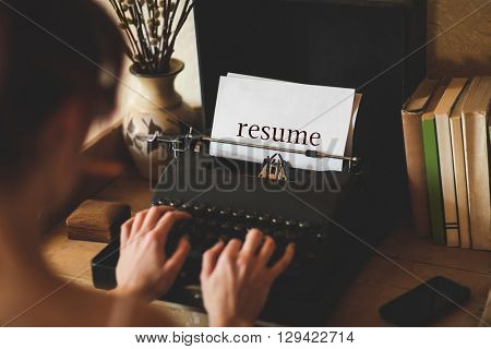 The word resume against young woman using typewriter