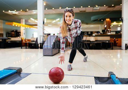 Woman throwing bowling ball in a bowling club