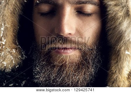 Portrait of a handsome brutal man with beard and mustache dressed in winter clothes, covered with frost. poster