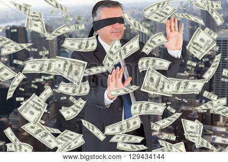 Mature businessman in a blindfold against view of cityscape