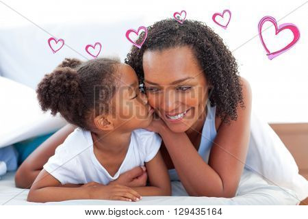 Red Hearts against cute little girl woman kissing her mother lying down on bed