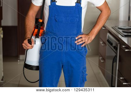 Midsection of pest worker with sprayer standing in kitchen