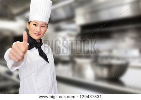 Smiling female cook gesturing thumbs up in kitchen against work surface and kitchen equipment