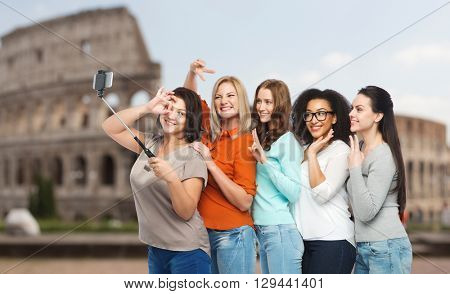 friendship, technology, travel, tourism and people concept - group of happy different size women in casual clothes taking picture with smartphoone on selfie stick over rome coliseum background