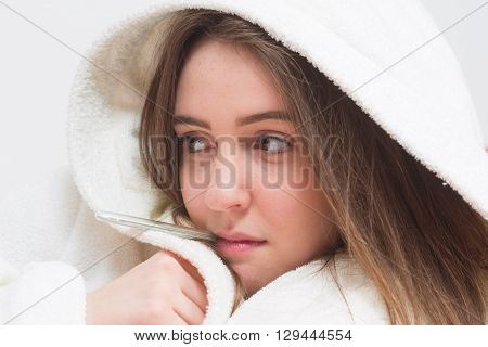 Sick teenager girl wearing bathrobe with fever