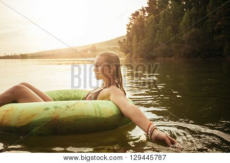 Young Woman In Lake On Inflatable Ring