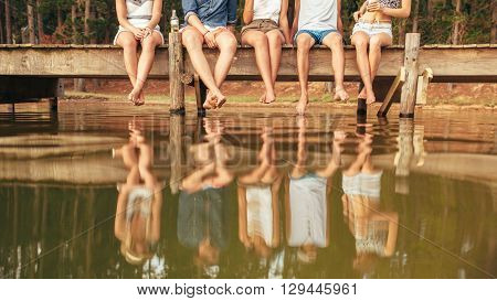 Young People Sitting On The Edge Of A Pier