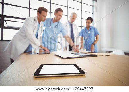 Digital tablet on table in conference room and medical team interacting in background