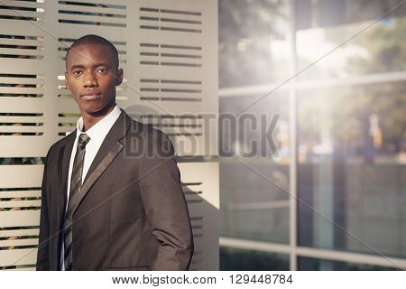 Portrait of a handsome young Businessman of African descent looking seriously at the camera while standing outside a modern office building