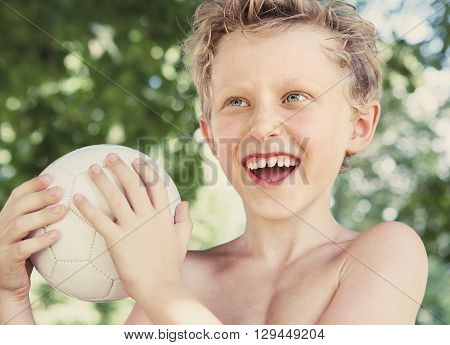 Happy smiling little boy summer portrait with a ball