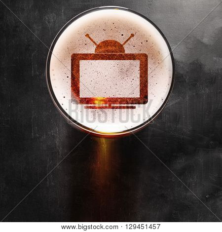 tv set symbol on foam in glass on black table, view from above