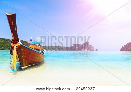 long boat at the beach with lens flare at koh Phi-Phi, Thailand