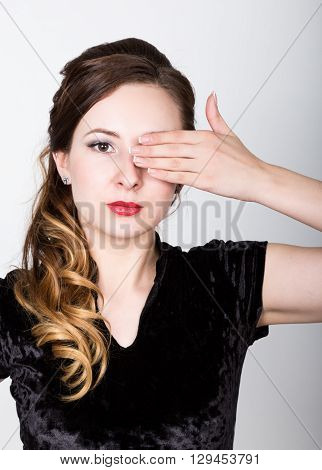 young woman's portrait with different happy emotions. girl closed her eyes with his hand.