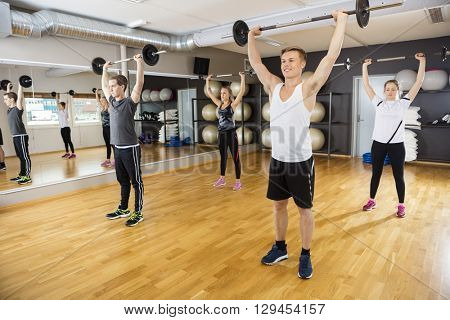 Men And Women Lifting Barbells In Fitness Club