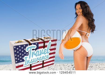 Travel insurance message on an american suitcase against pretty woman smiling and holding a beach ball