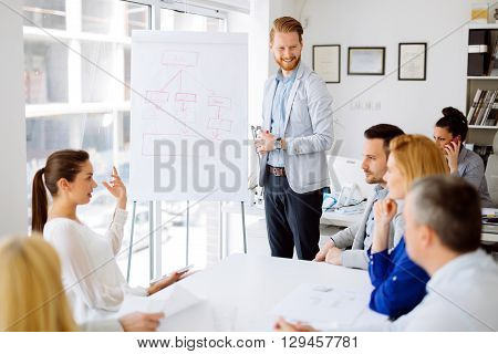 Business plan explained on flipchart by CEO to employees poster
