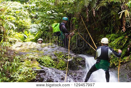 French West Indies Martinique islandSaut de gendarme waterfall-April 21 2016: The group of unidentified sportsmen making waterfall descent.