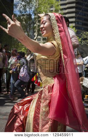 NEW YORK - APR 30 2016: A female dancer from NYC Bhangra performs in traditional clothing amongst the crowd at the Holi Hai Festival of Colors in Dag Hammerskjold Plaza in New York April 30, 2016.