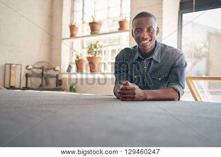 Portrait of a confident young business owner of African descent sitting in his workshop studio and smiling at the camera