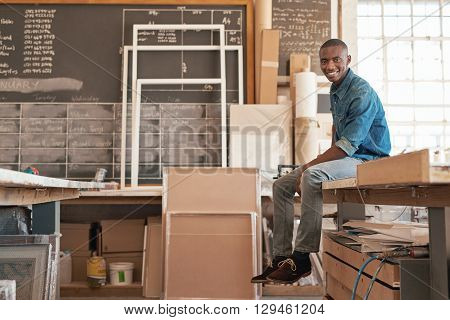 Portrait of a handsome young small business owner of African descent, smiling at the camera while sitting on the edge of a work bench in his studio workshop