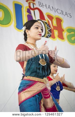 NEW YORK - APR 30 2016: A female dancer from NYC Bhangra uses the shikhara mudra, a hand gesture, while performing on stage at the Holi Hai Festival of Colors in New York on April 30 2016.