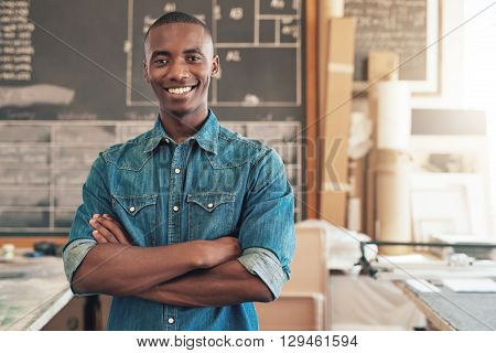 Portrait of a handsome young designer of African descent, smiling at the camera with his arms folded confidently, while standing in his studio