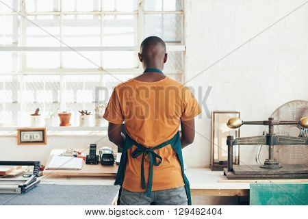 Back of young designer of African descent, standing at his work area in his workshop studio with beautiful light from large windows