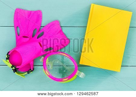Bright Flippers, Goggles And Book On A Green Table