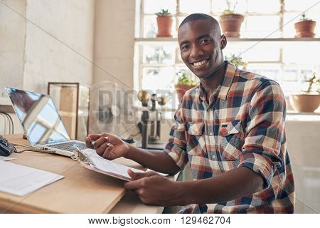 Portrait of a handsome young African entrepreneur and small business owner, sitting at a well lit desk in a contemporary studio, smiling at the camera while holding paperwork, with laptop open behind