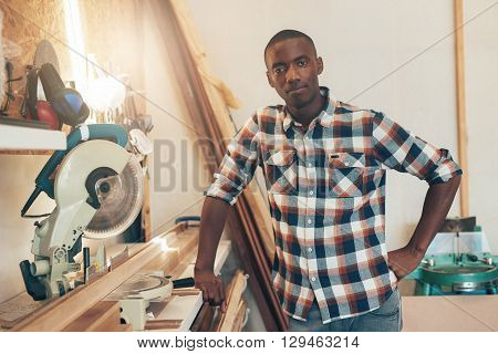 Portrait of a proud business owner of African descent, standing next to a new circular saw in his woodwork workshop, and looking proudly at the camera