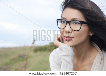 Portrait of a beautiful thoughtful chinese asian girl or young woman outside wearing glasses