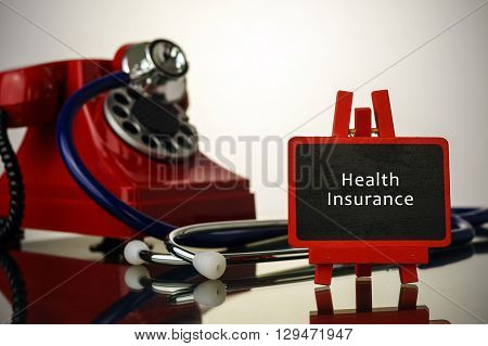 Medical Concept.phone And Stethoscope On The Table With Health Insurance Words On The Board.