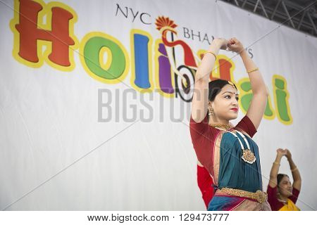 NEW YORK - APR 30 2016: A female dancer from NYC Bhangra uses mudras, or hand gestures, while performing on stage at the Holi Hai Festival of Colors in New York on April 30 2016.