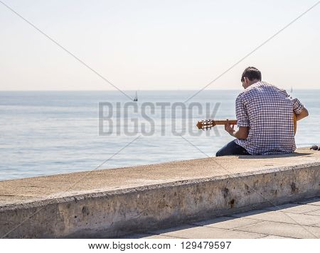 The Lonesome Musician in the Barcelona harbor