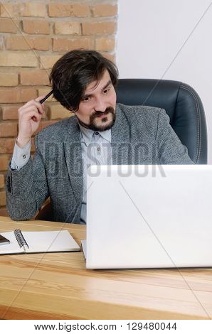 An Attractive Serious Thinking Businessman Having A Lot Of Work