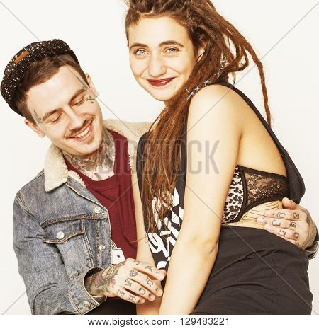 Young couple together making love, hugging. guy with tattoo, girlfriend wearing dreadlocks. Modern lifestyle concept, unsocial family